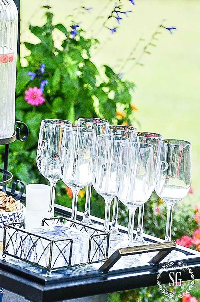 ROWS OF monnogrammed wine glasses on a bar cart