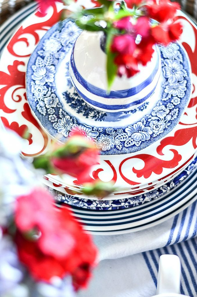 PRETTY STACK OF RED, WHITE AND BLUE DISHES ON A SUMMER TABLE