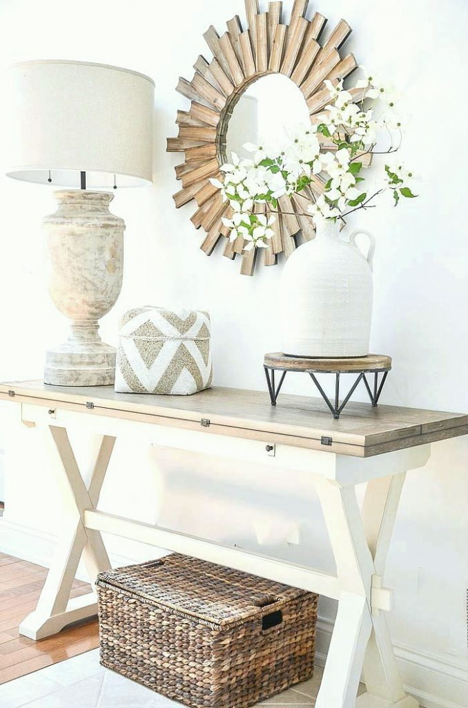 neutral color foyer table with a lamp and a sunburst mirror over it . A jug with flowers are opposite the lamp.