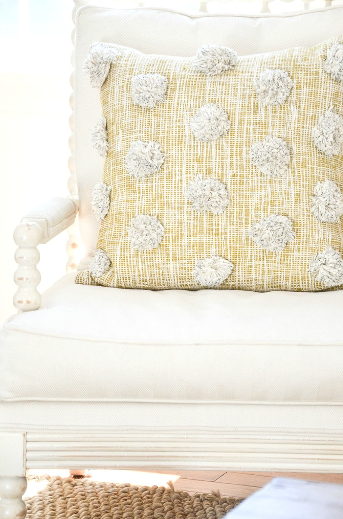 YELLOW PILLOW WITH POM POMS ON A WHITE CHAIR