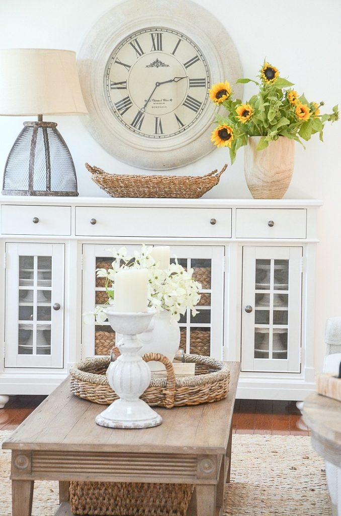 A BIG WHITE CLOCK OVER A WHITE BUFFET DECORATED FOR SUMMER