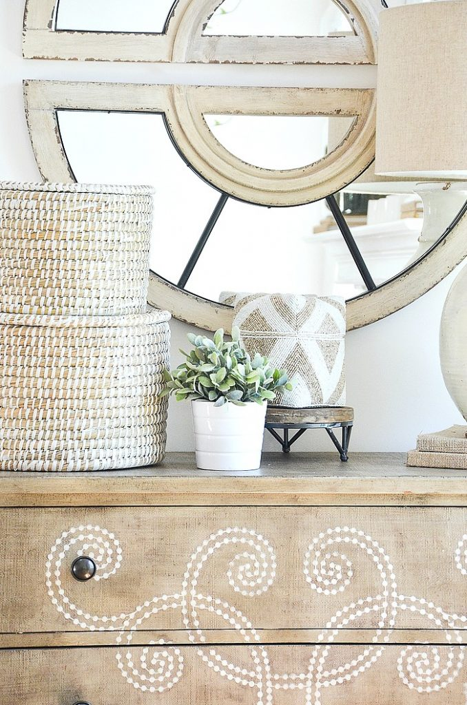 A stack of white baskets and other summer decor on a chest.