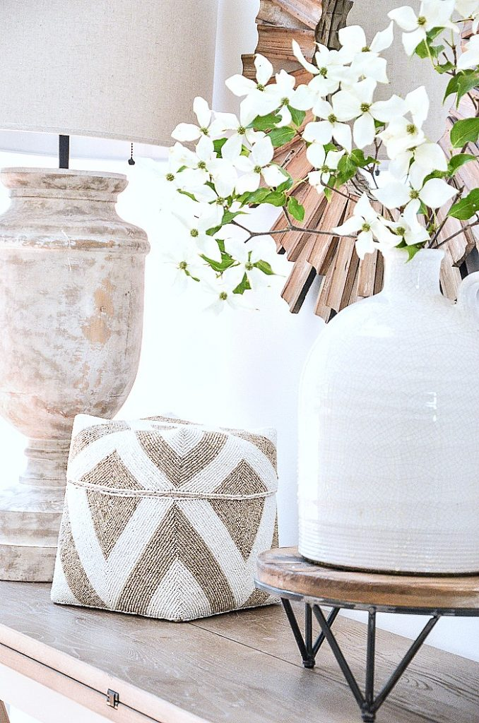 foyer table featuring a large white jug with Kousa dogwood branches