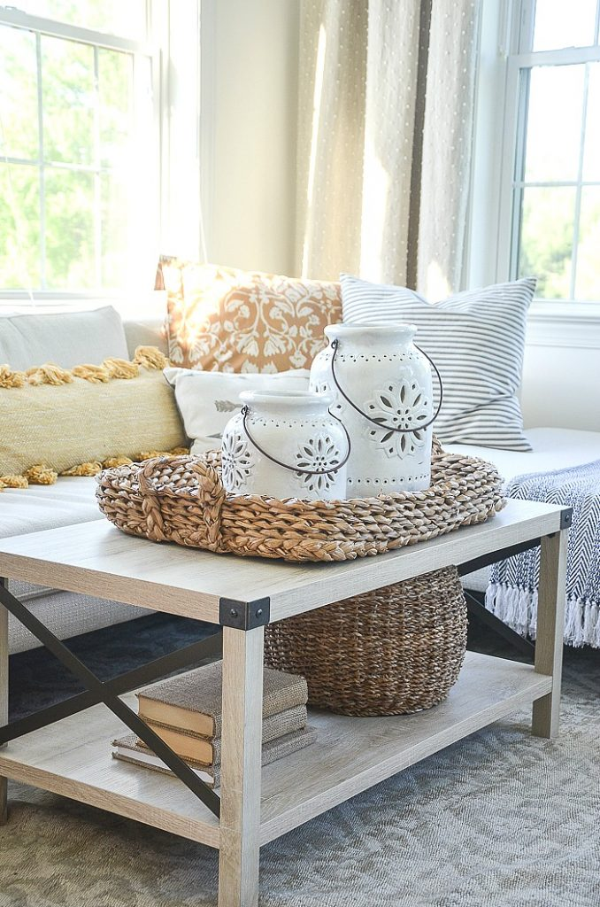 COFFEE TABLE WITH A BIG NUBBY BASKET WITH POTTERY LANTERNS IN IT