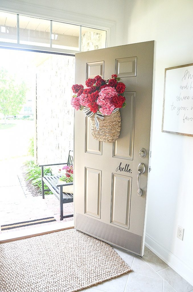FRONT DOOR  WITH A BASKET OF GERANIUMS ON IT