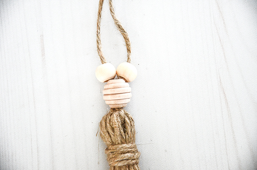 THE TOP OF A TWINE TASSEL WITH BEADS ON IT