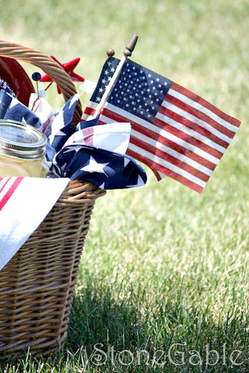 PICNIC BASET WITH AMERICAN FLAGS AND MASON JARS WITH LEMONADE