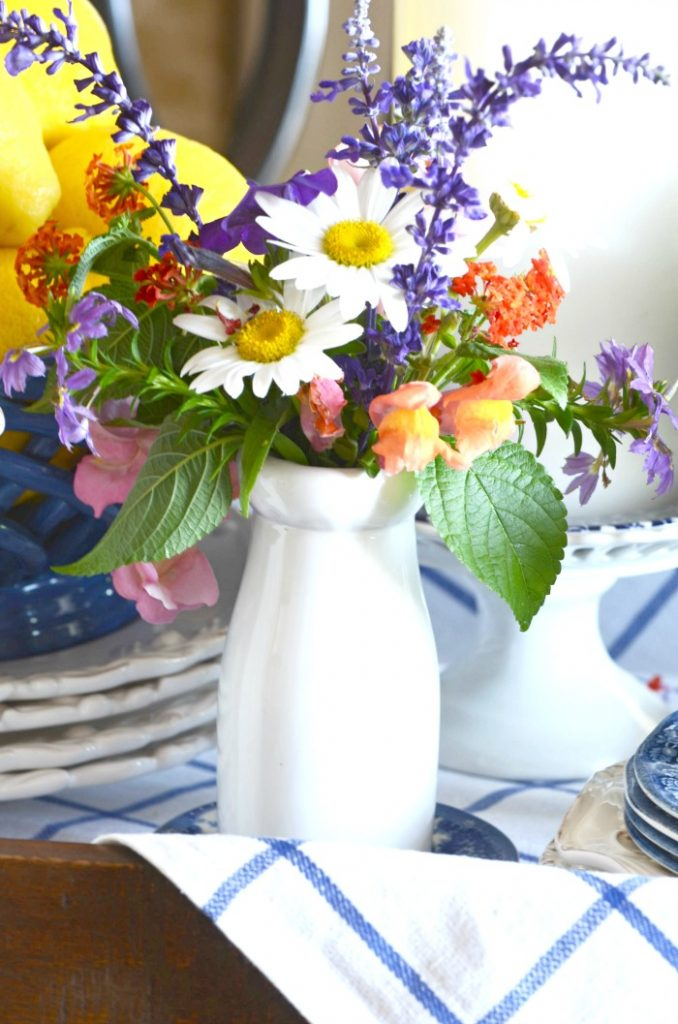 A SMALL WHITE MILK BOTTLE FILLED WITH GARDEN FLOWERS