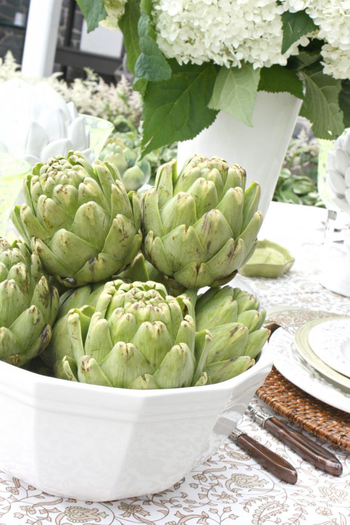 A BIG WHITE BOWL OF ARTICHOKES ON A SUMMER OUTDOOR TABLE