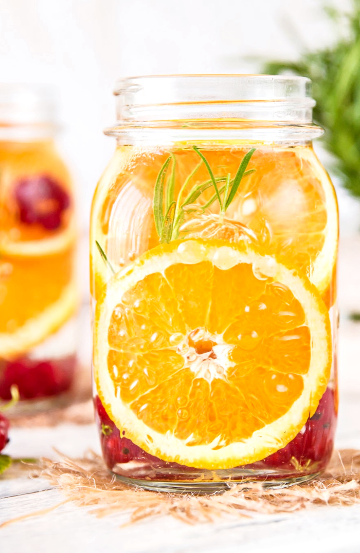 A BALL JAR OF HERB AND CITRUS FRUIT INFUSED WATER