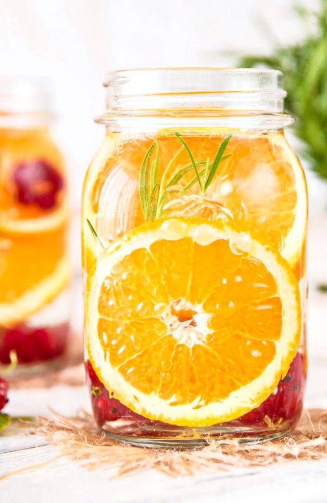 MASON JAR FILLED WITH CITRUS ROUNDS AND BERRIES