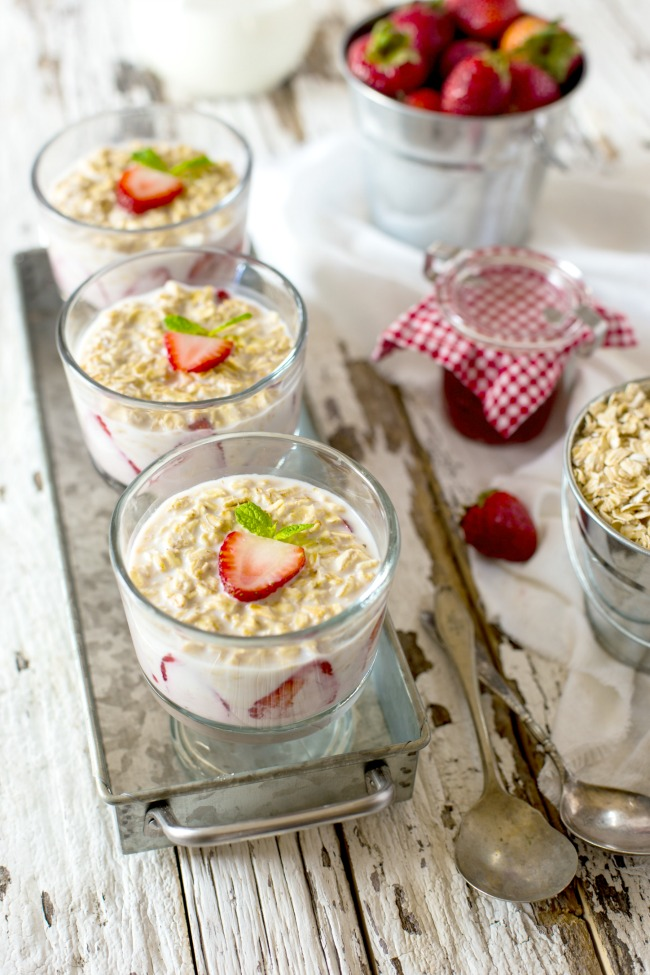 CLEAR GLASS JARS OF OATMEAL AND STRAWBERRY ON THE MENU