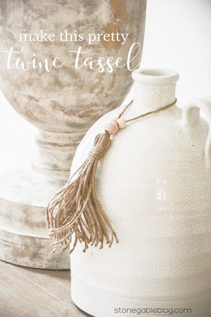 A JUG WITH A TWINE TASSEL TIED AROUND ITS THROAT