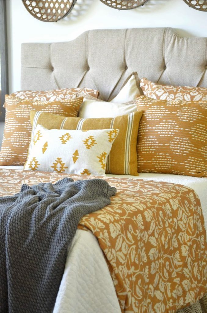 burnt yellow, white and gray bedding on a master bedroom bed