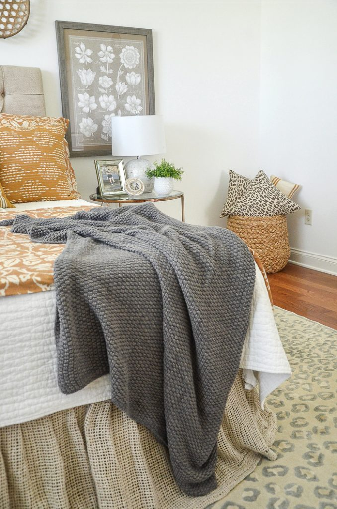 A BEDROOM DECORATED FOR SUMMER WITH SUMMER WHITE, GOLD AND GRAY BEDDING AND A BIG BASKET FILLED WITH MORE PILLOWS