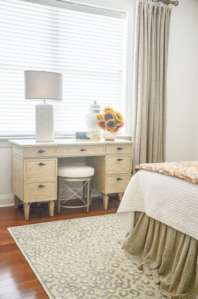a blond wood vanity with a white lamp and a vase of sunflowers on it. In a bedroom.