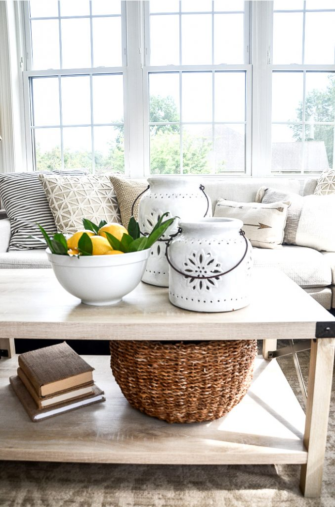 COFFEE TABLE WITH A BOWL OF LEMONS ON IT AND A BASKET ON THE SHELF BELOW