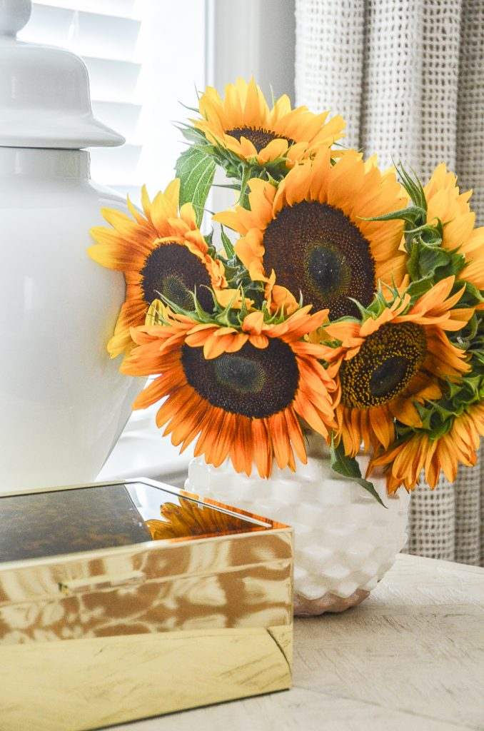 A big bouquet of sunflowers in a white vase sitting on a vanity in a bedroom