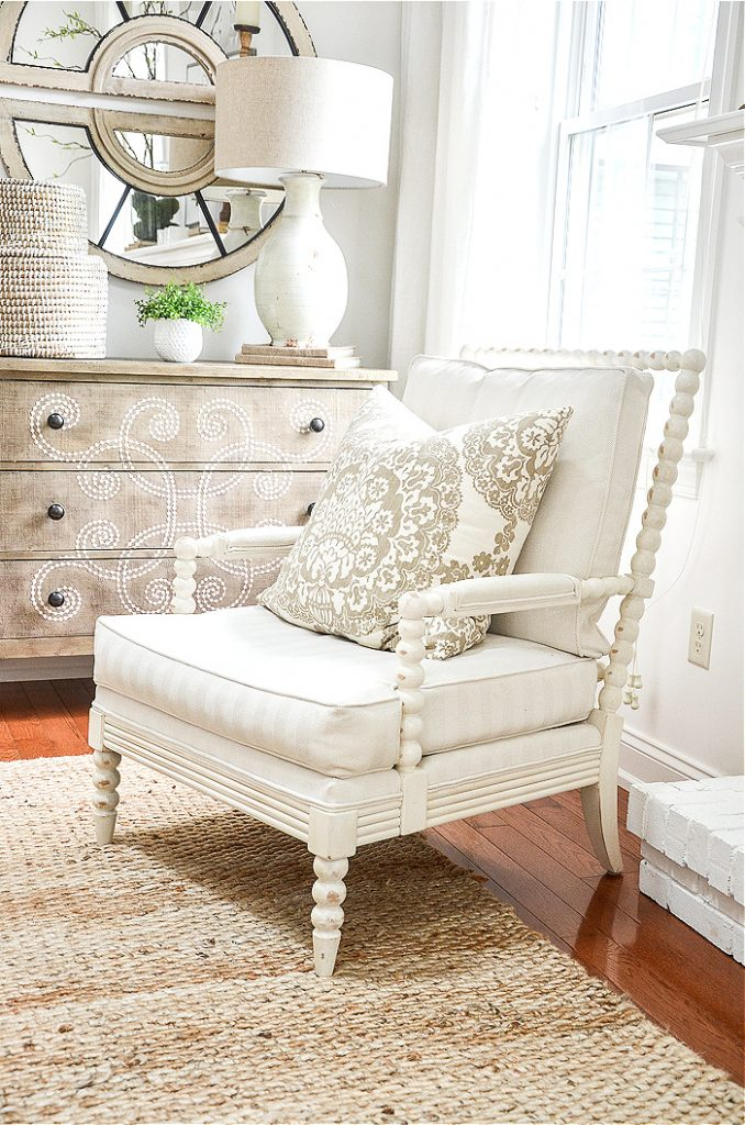 A white spindle chair and chest and mirror that was used in another part of the home but now are in the great room.