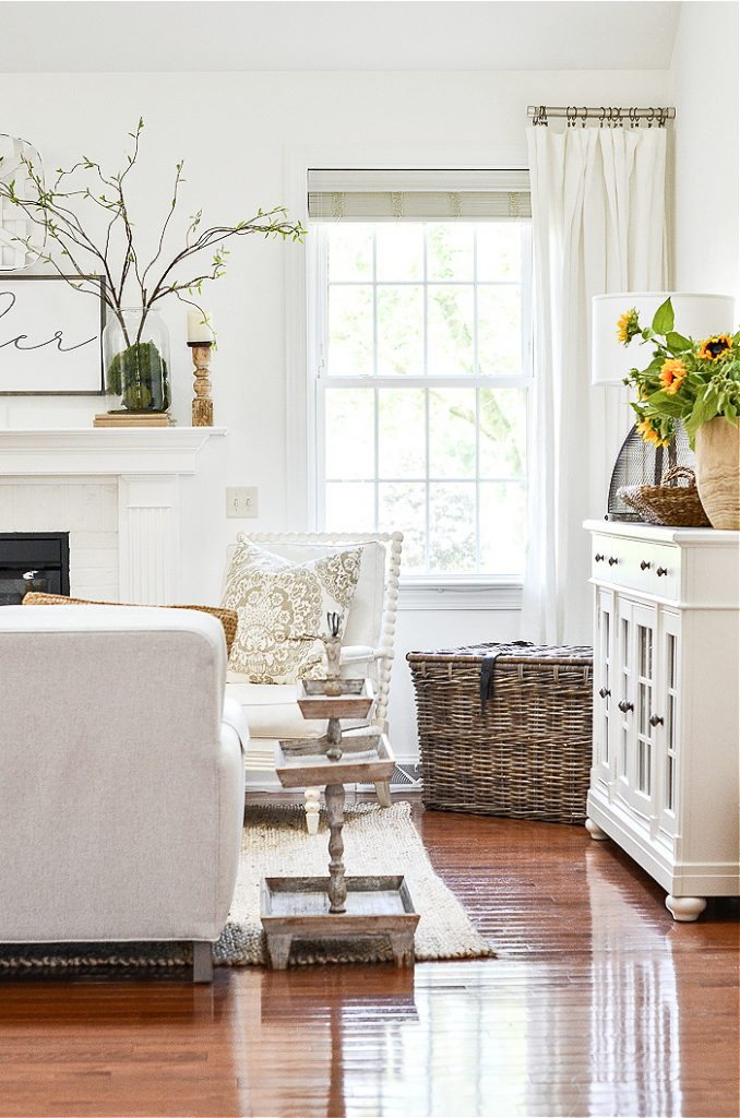 WHITE GREAT ROOM WITH POPS OF COLOR FROM A BIG CONTAINER OF SUNFLOWERS IN A WOODEN BOWL