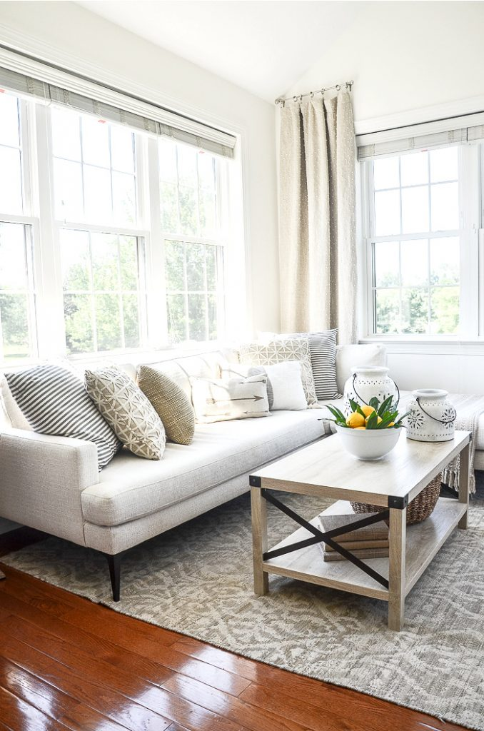 SUN ROOM WITH A LONG WHITE SECTIONAL AND COFFEE TABLE