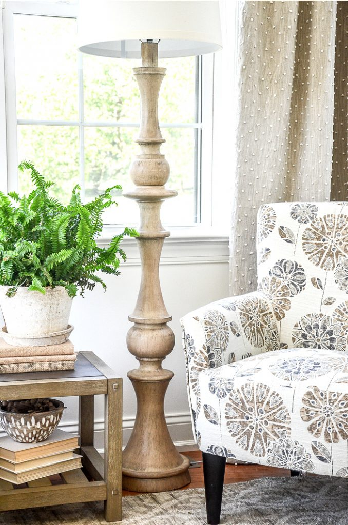 CLOSE UP OF A NEUTRAL COLOR CHAIR AND A TABLE WITH A FERN ON IT