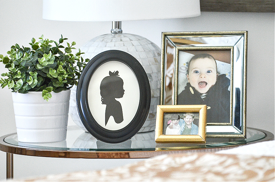 A NIGHT STAND NEXT TO A BED WITH A WHITE LAMP,. A GREEN PLANT AND FAMILY PICTURES ON IT