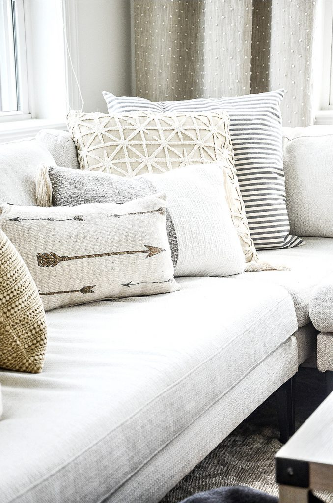 LOTS OF NEUTRAL PILLOWS ON A WHITE SECTIONAL
