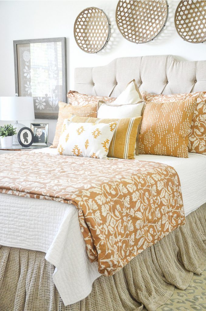 bed with a neutral color headboard and mustard yellow bedding