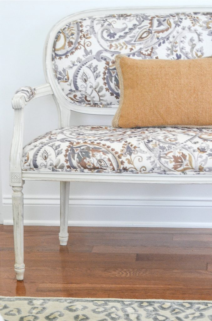 Italian settee with watercolor fabric in gray, white, brow and god with a gold burlap pillow
