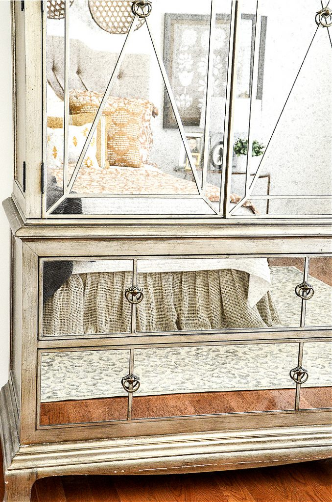 A BED REFLECTED IN A BIG MIRRORED ARMOIRE