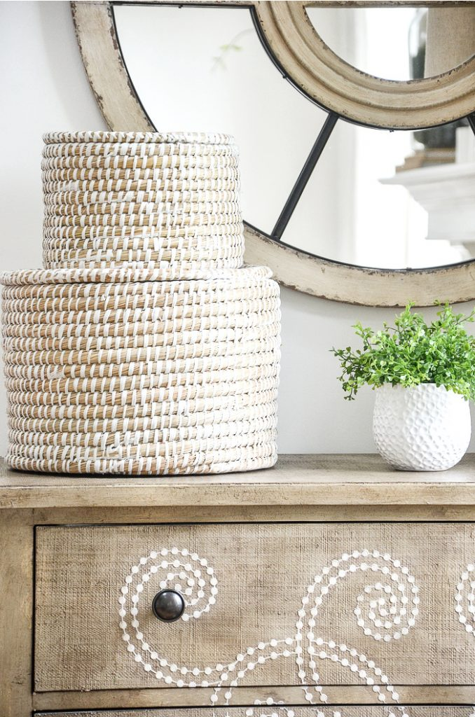 light colored rattan round boxes stacked on top of each other on a chest