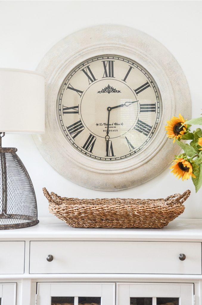 Big round wall clock that was once wood tone and now updated with white paint.