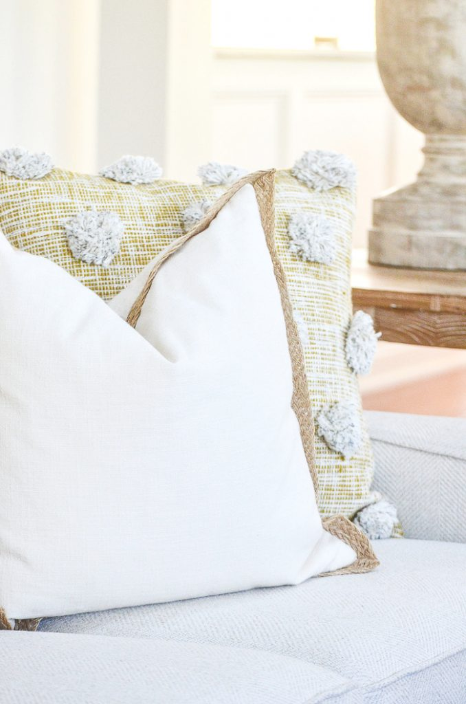 TWO LARGE PILLOWS ON A WHITE SOFA