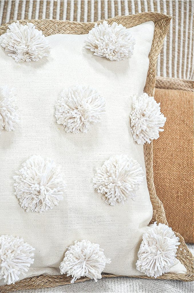 Trio of pillow on a sofa- featured pillow has pom-poms on the front of it