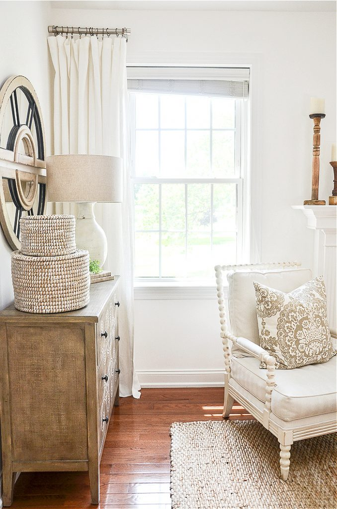 white linen curtains in a white painted great room. A pretty chest with a mirror above it is next to it.