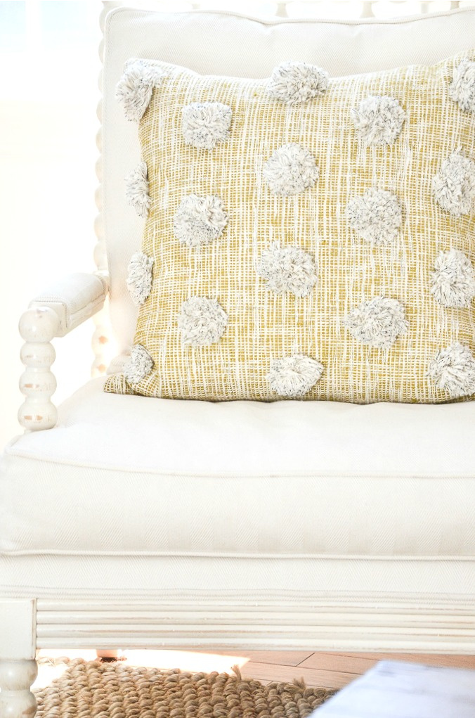 yellow pillow with pom-poms on the front of it.