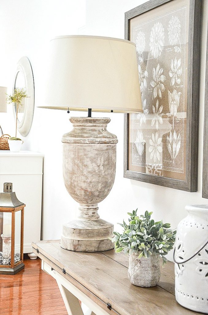 A large lamp and a picture behind it that was used in one part of the house but now is used in the foyer