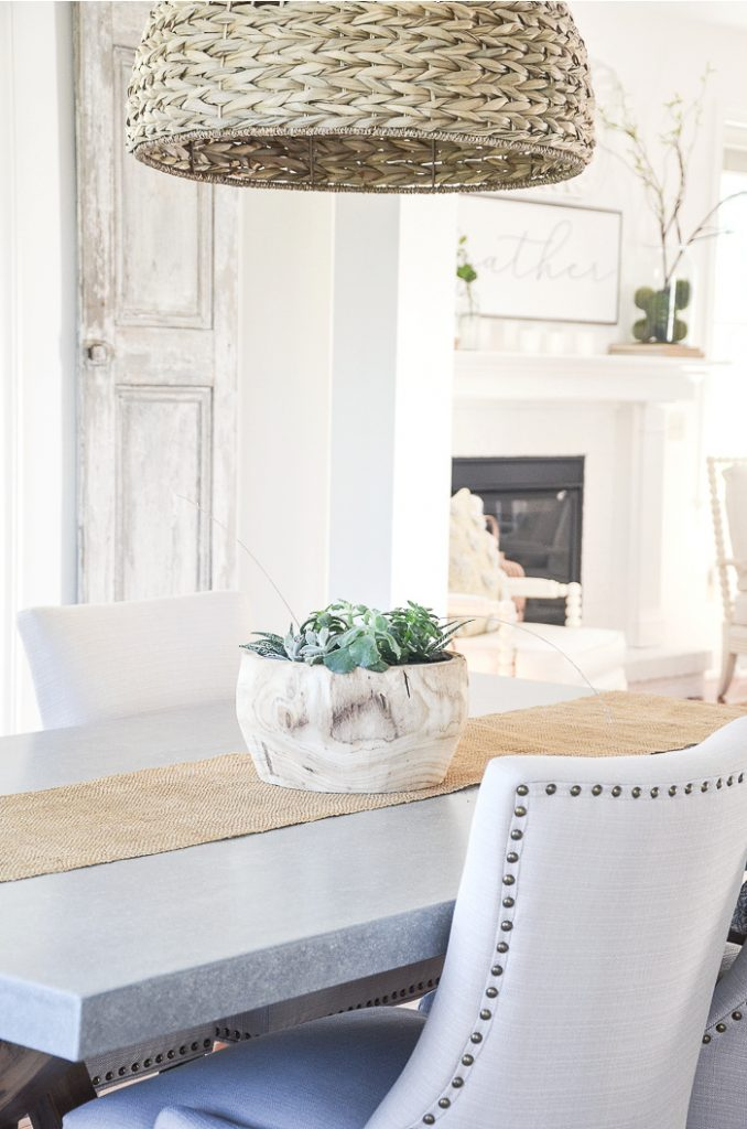 CONCRETE TOP DINING ROOM TABLE WITH A DOMED SEAGRASS PENDANT LIGHT ABOVE IT