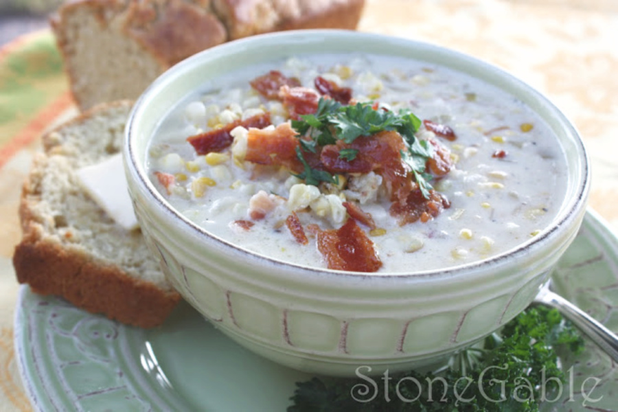 a bowl of fresh corn chowder on a green plate with a loaf of beer bread in the background.