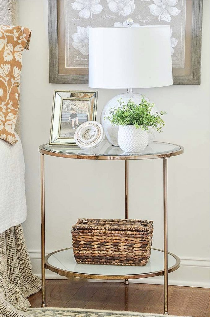 a night stand with a round white lamp on it and a green plant and family pictures.