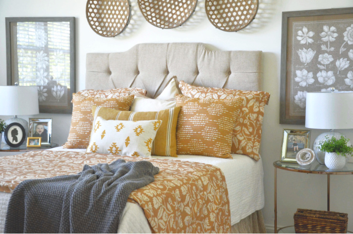 summer bedroom with bed, baskets above the bed and night stands.