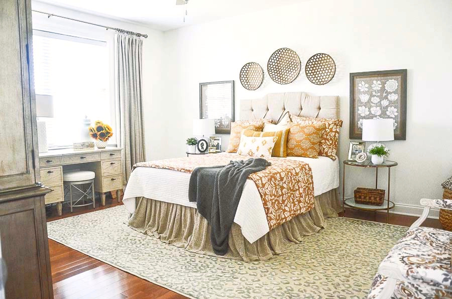 a bedroom with a bed decorated with white, god and gray bedding- an Italian settee and a vanity.