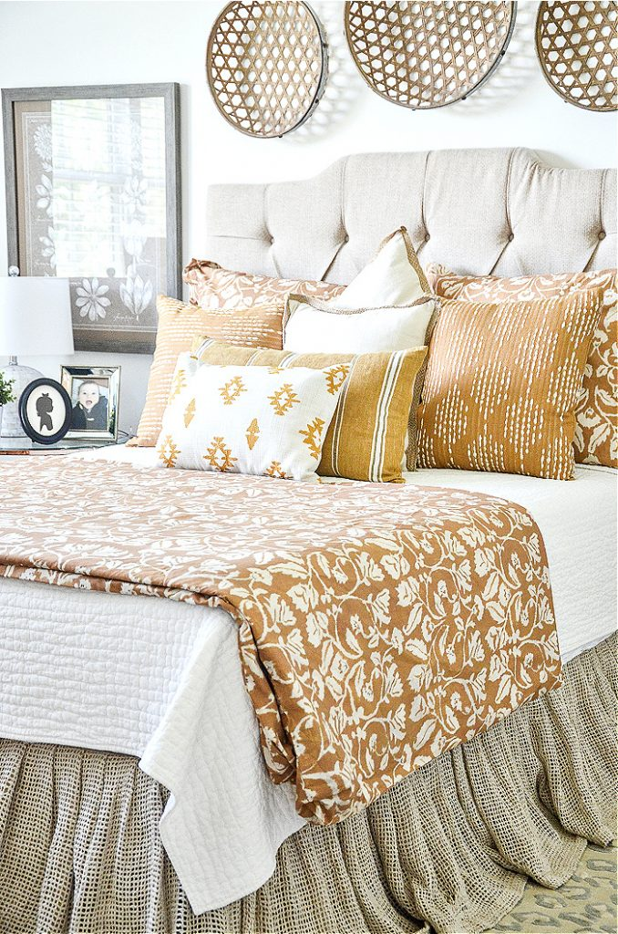 tall neutral upholstered headboard in a master bedroom