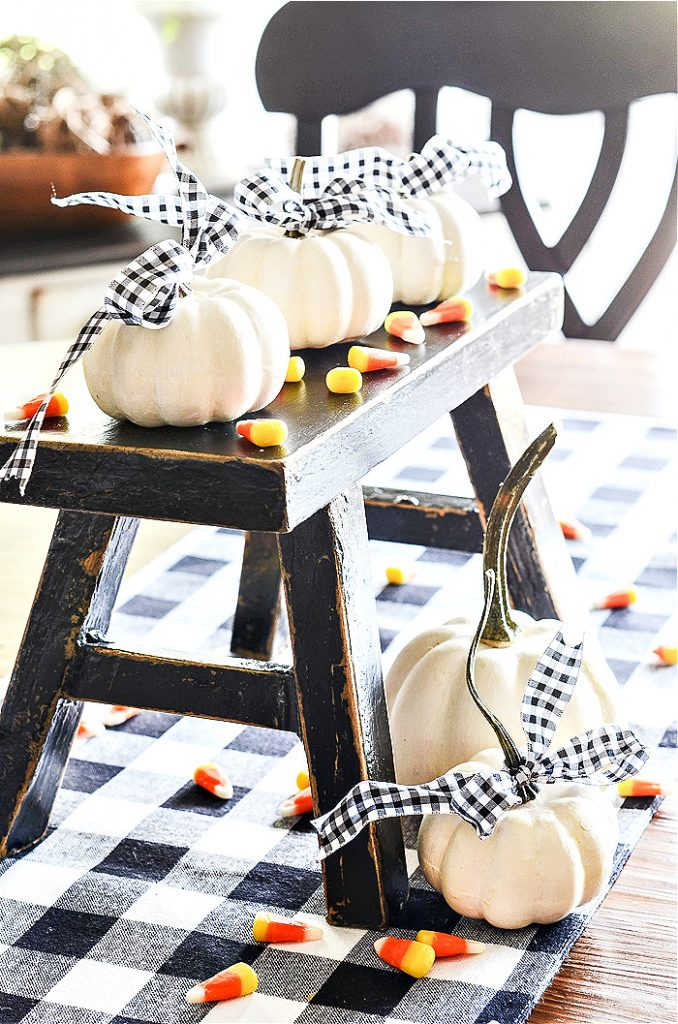 WHITE PUMPKINS STYLED ON A BLACK STOOL