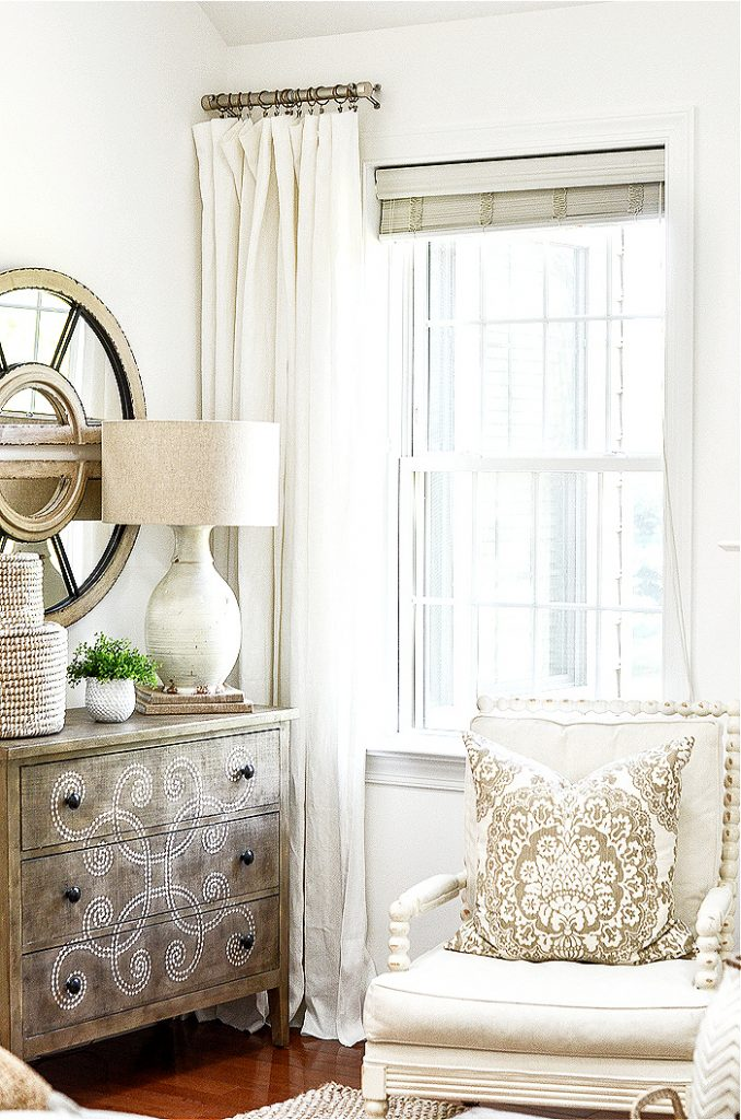 a chair, dresser and curtains that have a mix of metals embellishing them
