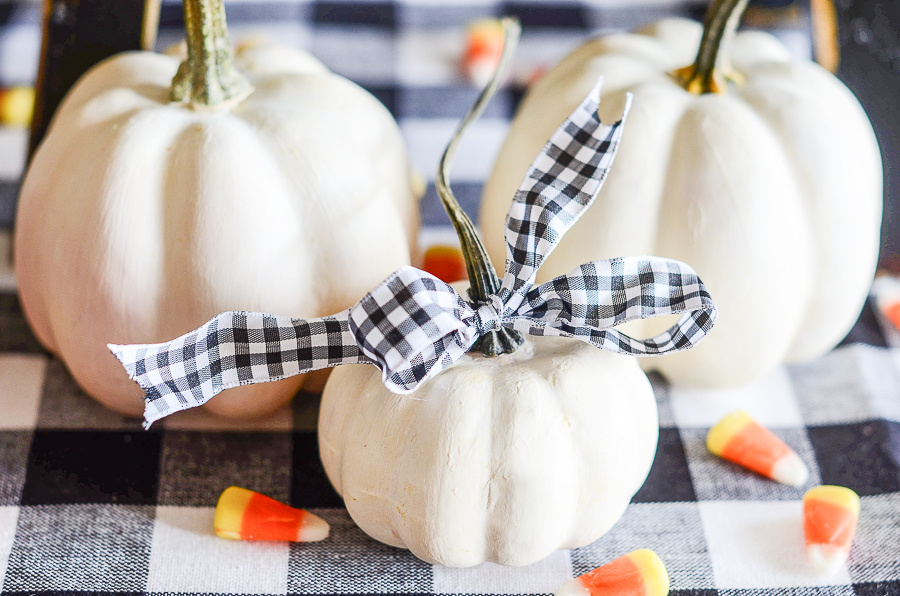 A TRIO OF WHITE PAINTED PUMPKINS WITH REAL STEMS AND A BLACK AND WHITE RIBBON