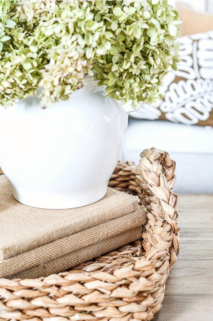 A BASKET WITH BURLAP COVERED BOOKS AND A VASE OF DRIED HYDRANGEAS IN IT