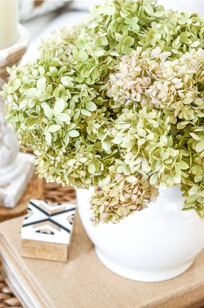 A WHITE VASE OF HYDRANGEAS ON A STACK OF BURLAP COVERED BOOKS
