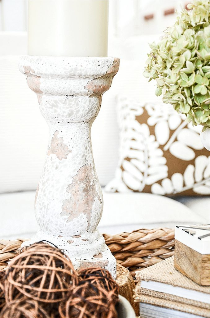 A CHIPPY CANDLESTICK SURROUNDED BY WILLOW BALLS IN A BASKET COFFEE TABLE VIGNETTE